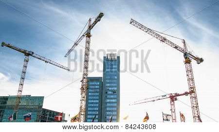 Building Under Construction And Crane Around Against Blue Sky. Background