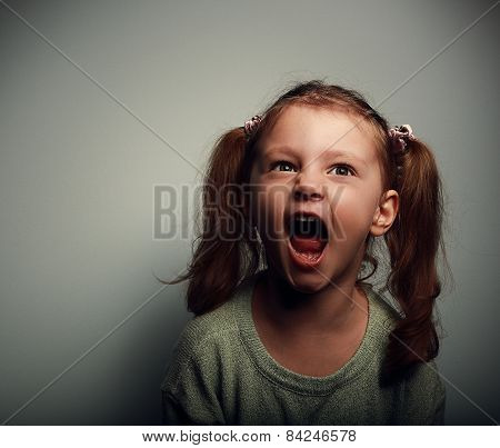 Shouting Angry Kid Girl With Open Mouth And Negative Look On Dark Background