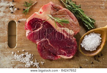 Raw Beef T-bone Steak On A Old Wooden Board