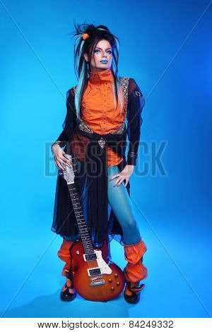 Punk Rock Girl Guitarist Posing Over Blue Studio Background. Trendy Model With Hairstyle.