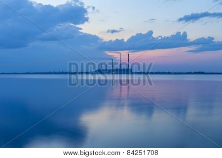 Thermal power plant and the lake at sunset