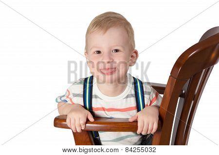 Portrait Of Little Boy Sitting On A Chair