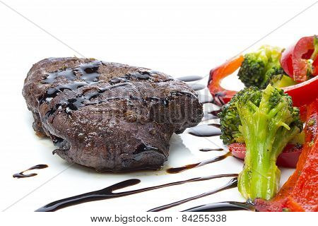 A Beef Stake With Steamed Green Arranged On A White Plate