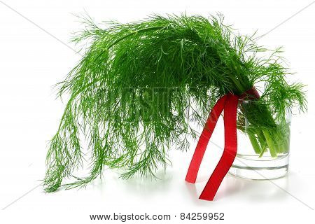 Dill Bunch With A Red Ribbon In A Glass With Water, Isolated On White
