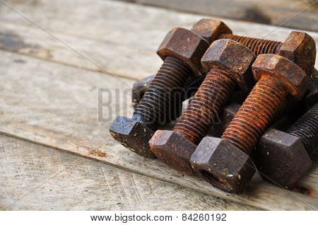 Old bolts or dirty bolts on wooden background, Machine equipment in industry work