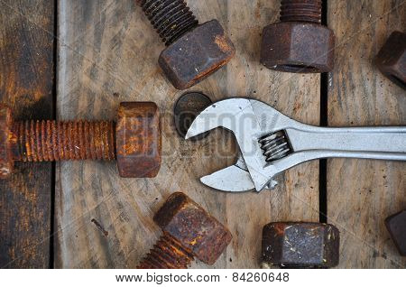 Old bolts with adjustable wrench tools on wooden background.