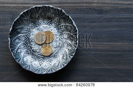small textured metal plate with euro coins on a wooden background