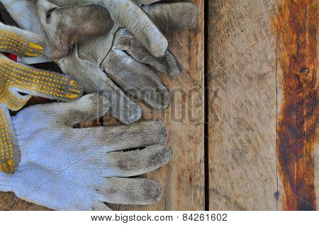 Old safety gloves on wooden background, Gloves on dirty works.