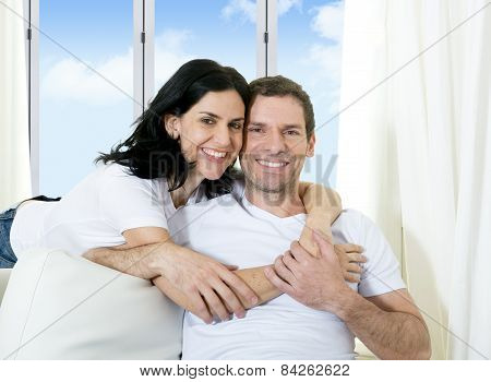 Young Attractive Brazilian Couple With Woman Hugging His Husband In Couch
