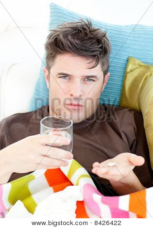 Sick Caucasian Man Holding Pills And Water Looking At The Camera