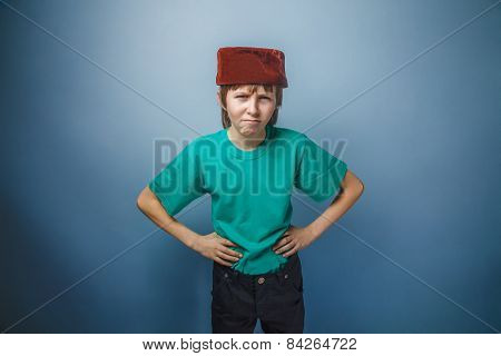 Muslim boy of ten years, skullcap, unhappy on a gray background