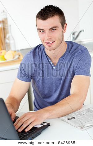 Handsome Young Man Using His Laptop Looking At The Camera
