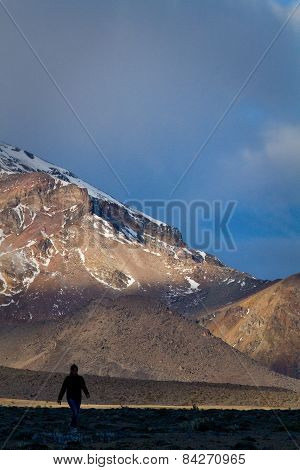 Tourist sillhouette walking along Chimborazo National Park in andean Ecuador