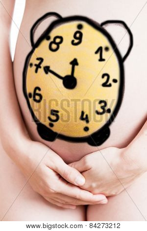 Belly of a pregnant woman with pregnancy clock