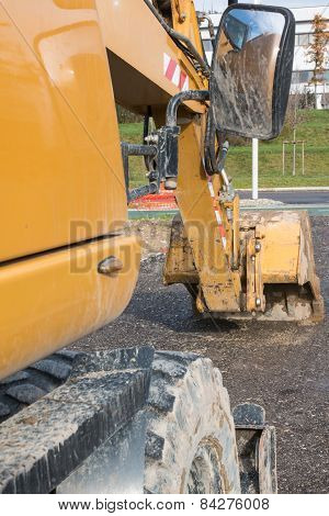Muddy Excavator Shovel With Rear-view Mirror At Construction Area