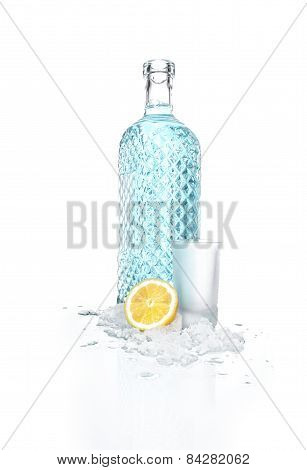Bottle Of Vodka With Small Beaker Glass And Lemon, Isolated On White