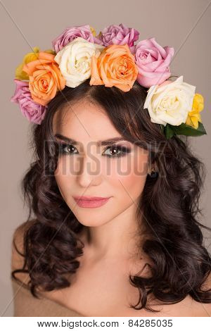 Portrait of a beautiful young woman with a wreath of delicate roses on her head.