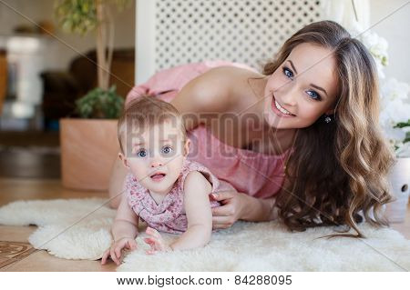 Happy mother and baby daughter playing and having fun at home.
