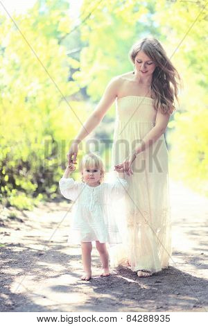 Sunny Photo Mother And Child Walking Barefoot In The Forest, Mom Helps The Baby To Take The First St