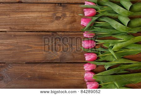 Bouquet of beautiful pink tulips on an old wooden floor.