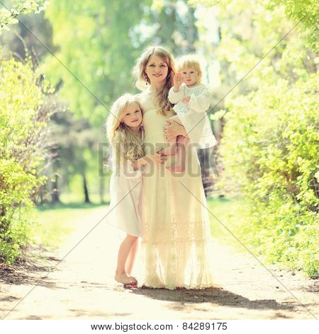 Sunny Portrait Of Happy Family On The Nature, Young Mother Hugging Her Two Daughters In Summer Day