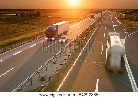 Trucks And Car On The Highway At Sunset