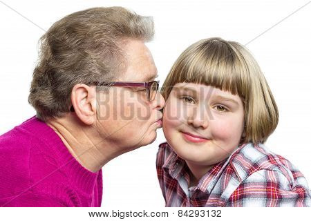 Grandmother kisses granddaughter on cheek