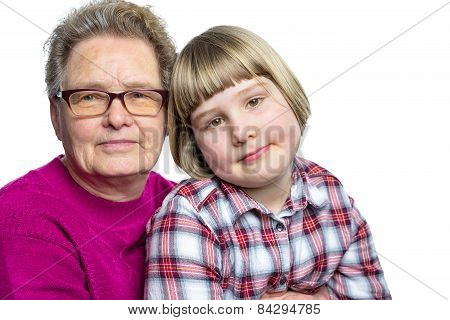 Granddaughter sitting on lap of grandmother on white background