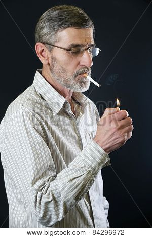 Senior man lighting cigarette