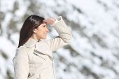 foto of forehead  - Woman looking forward with the hand on forehead in winter holidays with a snowy mountain in the background - JPG