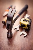 stock photo of hand tools  - Close up Head of a Claw Hammer Hand Tool on Top of a Wooden Table with Other Hand Tools on the Sides - JPG