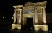 image of gate  - night view of the Puerta del Puente  - JPG
