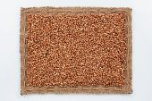 picture of buckwheat  - Frame of burlap and buckwheat grain lying on a white background - JPG