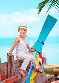 picture of old boat  - cute kid boy sitting on old boat on tropical beach - JPG