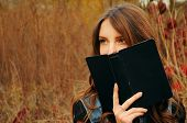 image of auburn  - cute young woman with long auburn hair in the autumn forest reading a book - JPG