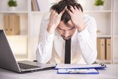 foto of frustrated  - Frustrated middle aged businessman sitting at office desk - JPG