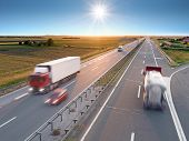 stock photo of cistern  - Trucks and car in motion blur on the highway towards the rising sun - JPG