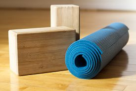 foto of studio  - A blue yoga mat with two wooden yoga blocks sit on a wooden yoga studio floor before class - JPG