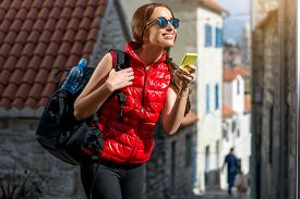 stock photo of sportswear  - Young woman in red sportswear looking where to go with smart phone traveling in the old city center - JPG
