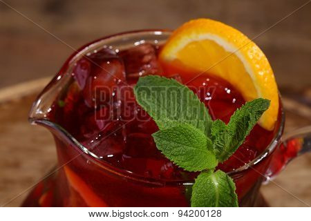 Wine Of Sangrija With An Orange In A Transparent Jug On A Wooden Table