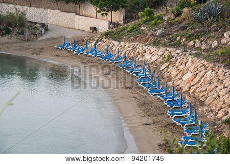 Line Of Empty Sunbeds On On A Beach