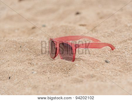 Pink Sunglasses Left On A Sandy Beach