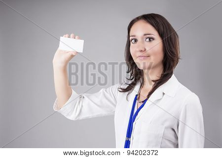 Young Medical Female Doctor Presenting And Showing White Card For Product Or Text. Caucasian Medical