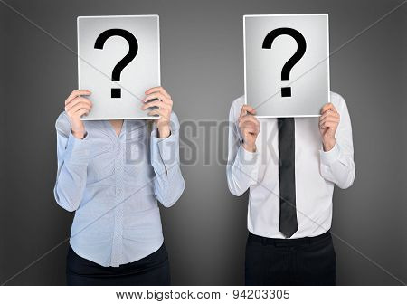 Question mark on paper in hands of business woman and man