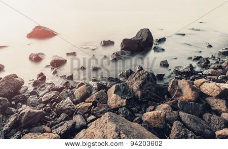 Vintage Stones on a background of blurred sea with mountain views