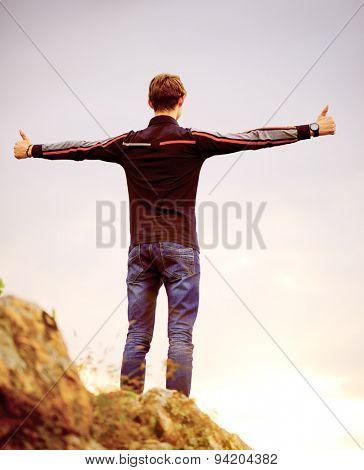 Young Man Standing on the Mountain Peak with Arms Raised. Active Lifestyle Concept.