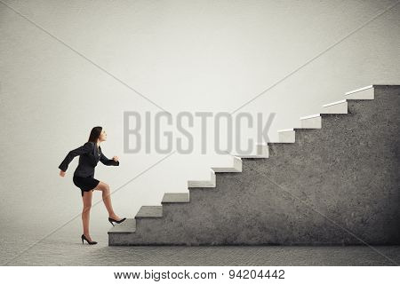 purposeful woman in formal wear walking up stairs over light grey background