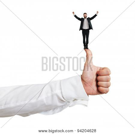happy small businessman standing on big thumbs up and raising his hands up. isolated on white background