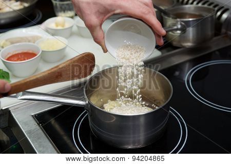 Chef is pouring rice in stewpan to cook risotto