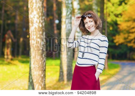 Fashion And Style Concepts: Smiling Caucasian Brunette Woman With Sun-glasses Posing In Forest